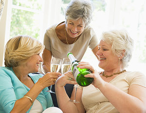 Three Seniors in living room drinking champagne and smiling
