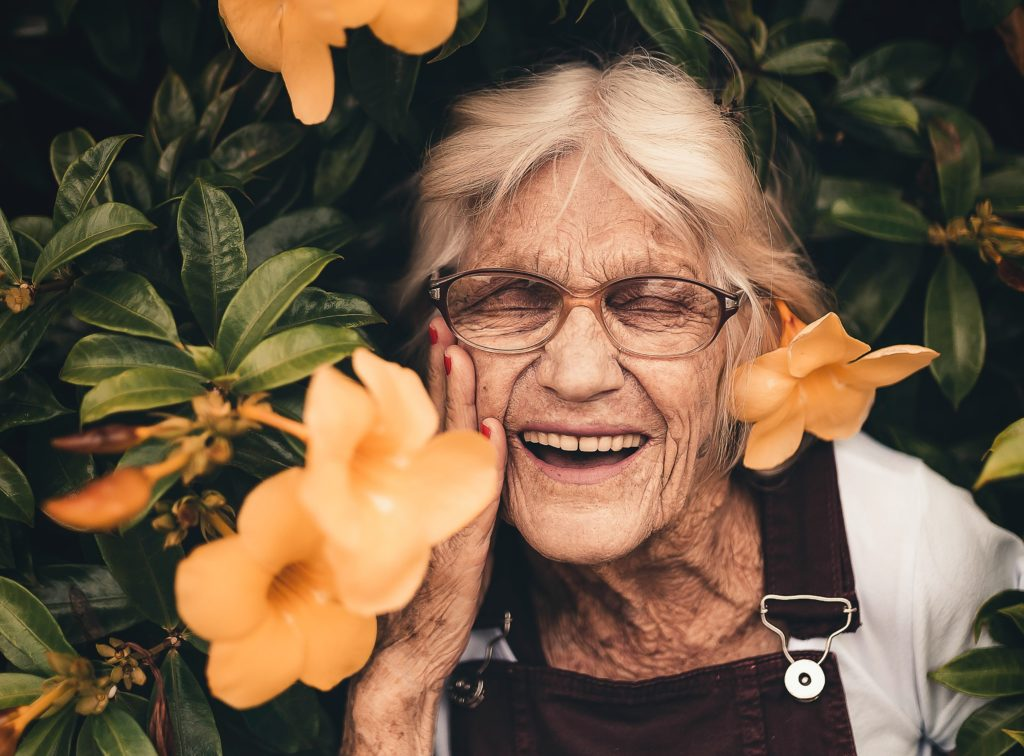 Elderly woman smiling amongst flowers in the garden
